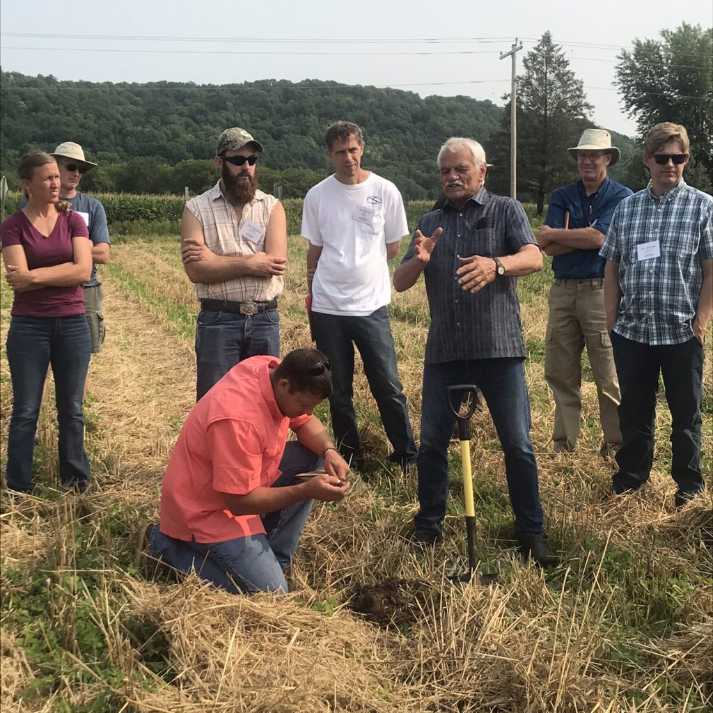 Gary Zimmer stands in cover crop field surrounded by On-Farm Intensive attendees.